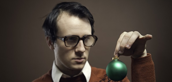 It's Christmas time, and a nerdy young man wearing big glasses and a retro sweater contemplates where to hang his green bauble ornament.  Shot indoors on a horizontal brown background with copy space.